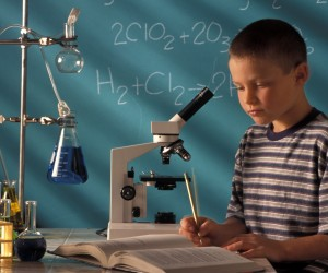 Boy Taking Notes From Textbook In Chemistry Class